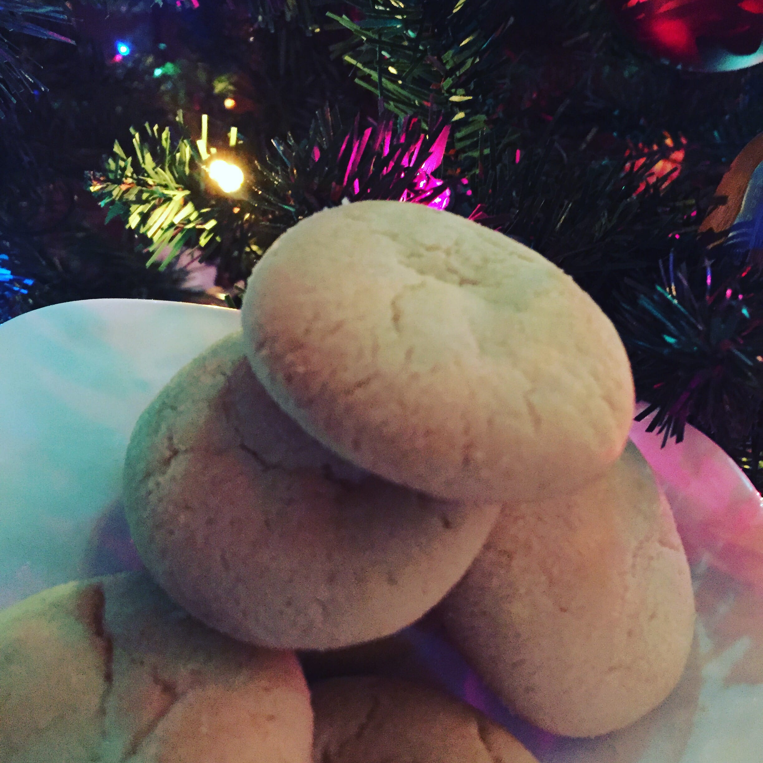 Baked sugar cookies stacked on a white plate in front of a lighted Christmas Tree