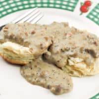 close up of biscuits and gravy on white plate with green plaid rim with fruit detail