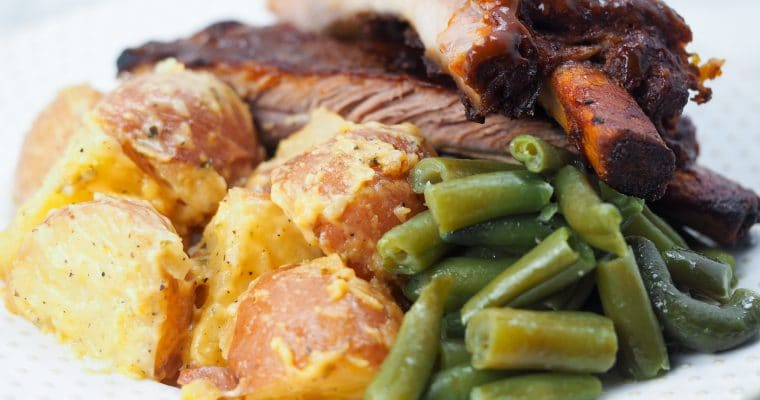cheesy potatoes with ribs and green beans on white plate