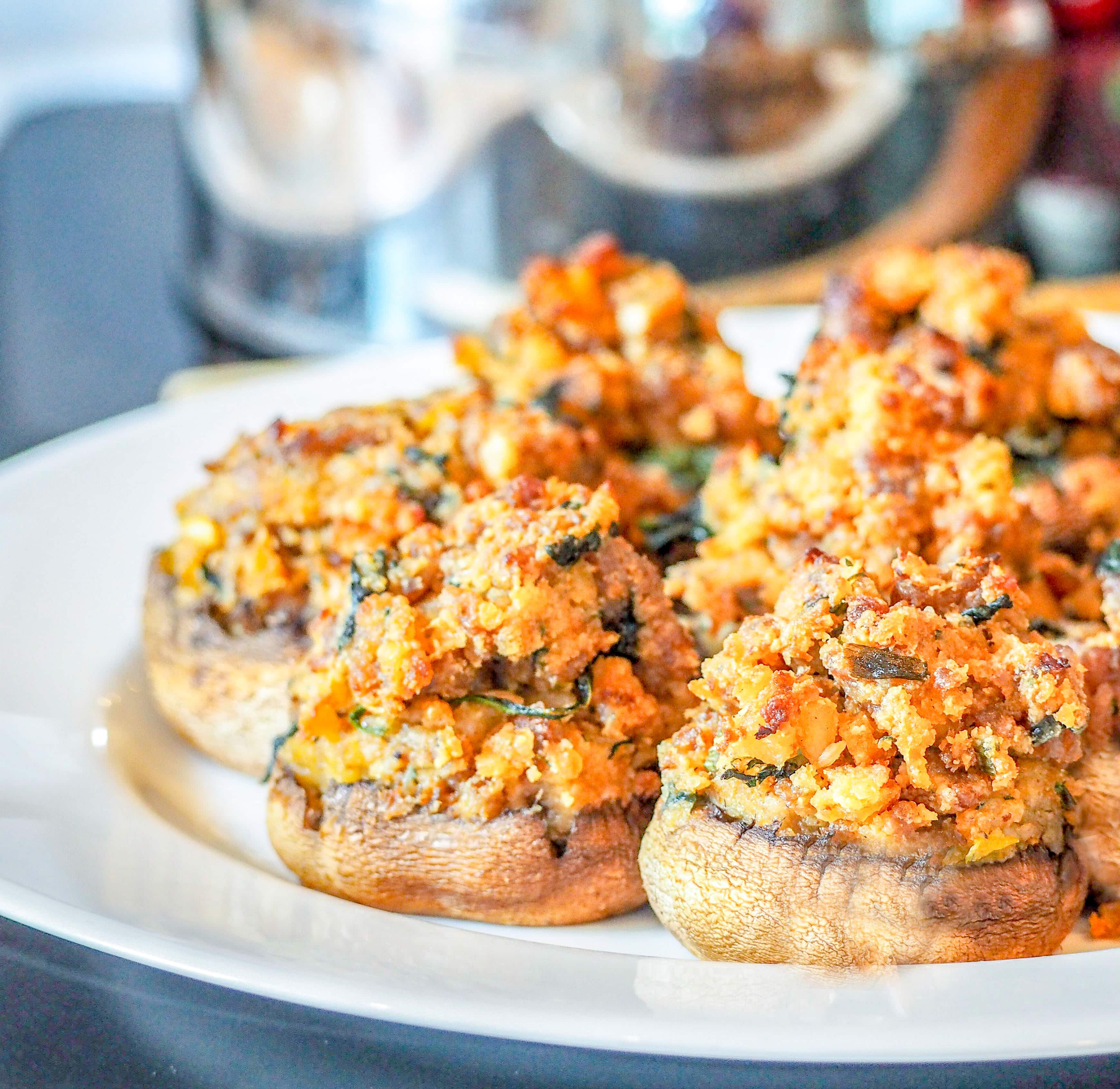 italian sausage stuffed mushrooms on a white plate sitting on a stove with a teapot in the background