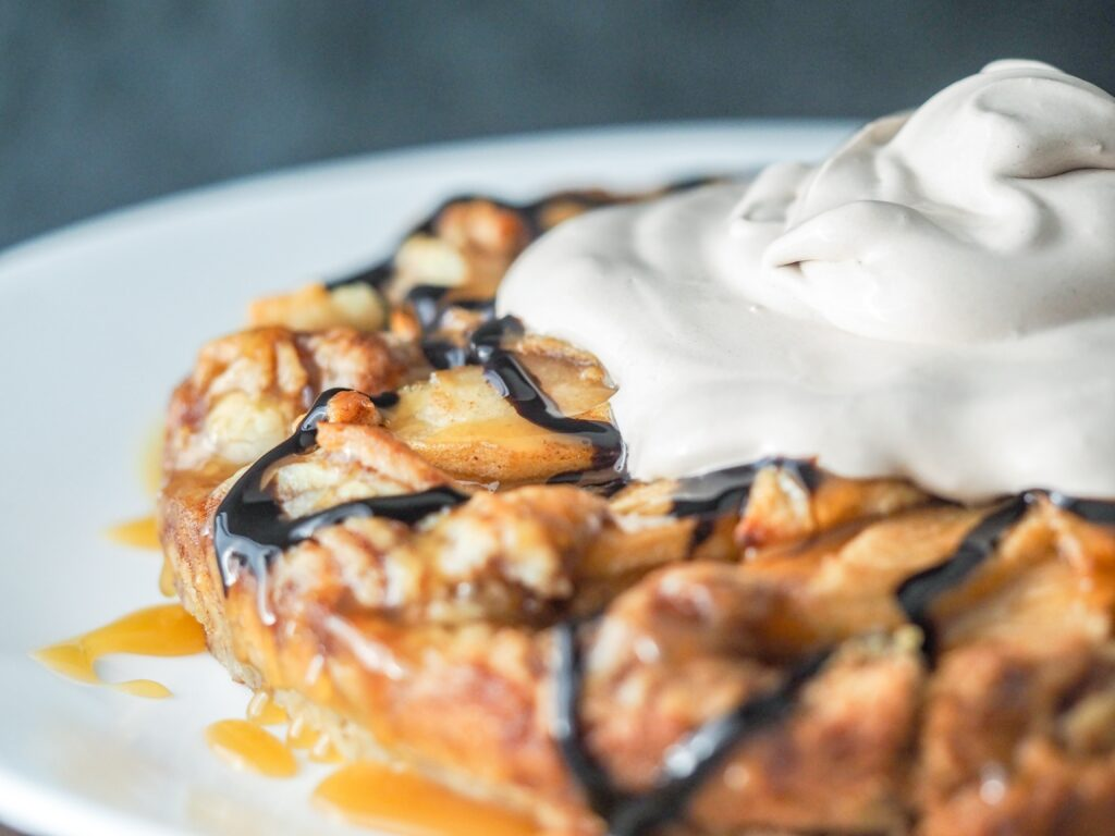 apple galette with cinnamon roll pie pastry on a white plate drizzled with caramel and chocolate syrup topped with chocolate whipped topping