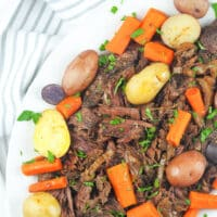 pot roast on platter with potatoes and carrots