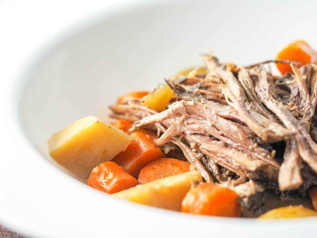 close-up view of shredded chuck roast with potatoes and carrots in a white bowl with a large rim