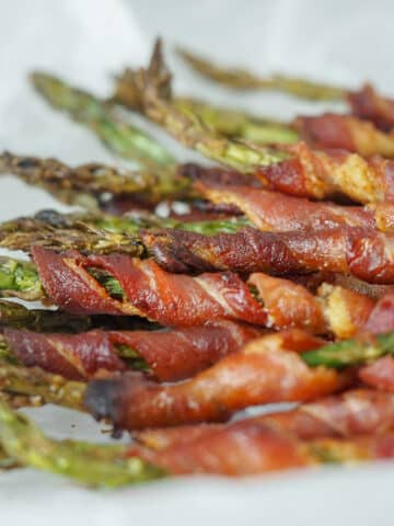 bacon wrapped asparagus laying on parchment paper