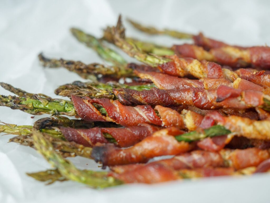 bacon wrapped aspargus spears laying horizontally on white parchment paper at close view