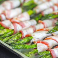 bacon wrapped asparagus spears bundled toghether with bacon on an aluminum tray