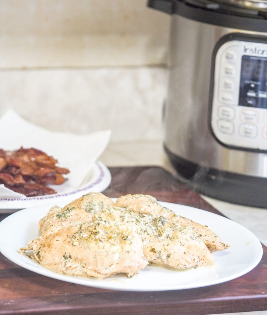 cooked seasoned chicken on white plate sitting on a mahogany cutting board with instant pot in background to the right and plate of cooked chicken to the left