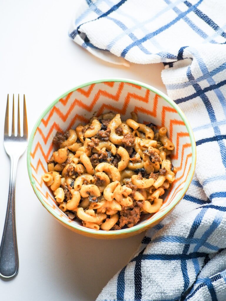 overhead shot of cheeseburger macaroni and cheese in white orange striped bowl with blue and white towel with fork to left