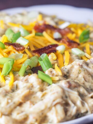 close up of instant pot crack chicken on white platter topped with sliced green onions shredded cheese and crumbled bacon