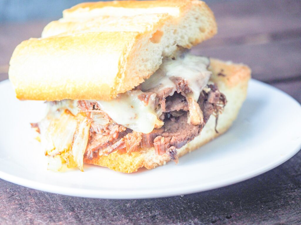 french dip sandwich on white plate on wooden table