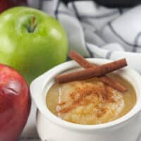 applesauce in white bowl next to red and green apples
