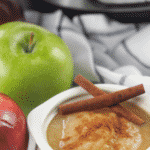applesauce in white crock with fresh apples