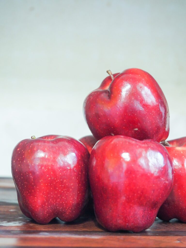 stack of red delicious apples sitting on a wet cutting board
