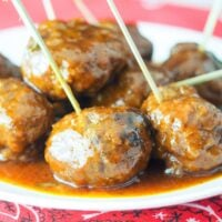 close up view of bbq meatballs on white plate sitting on red bandana