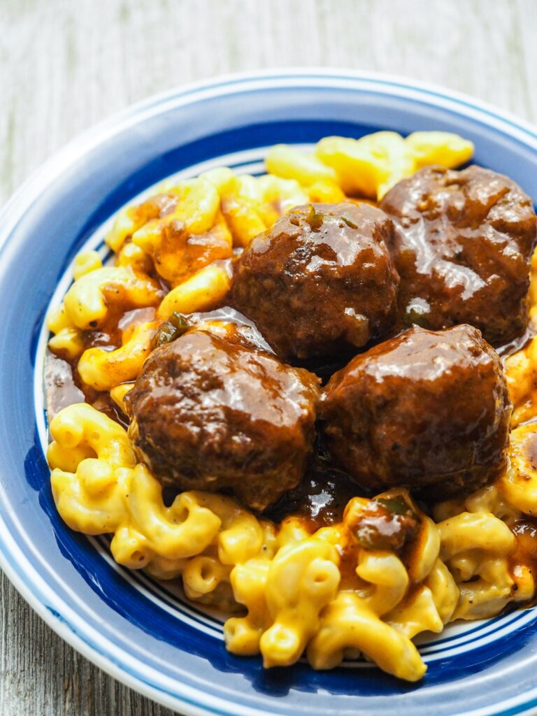 close up view of mac and cheese topped with bbq meatballs on a white plate with blue rim