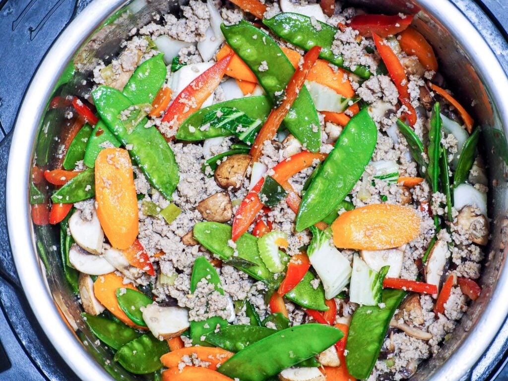 overhead shot of ground pork stir fry in instant pot with fresh vegetables