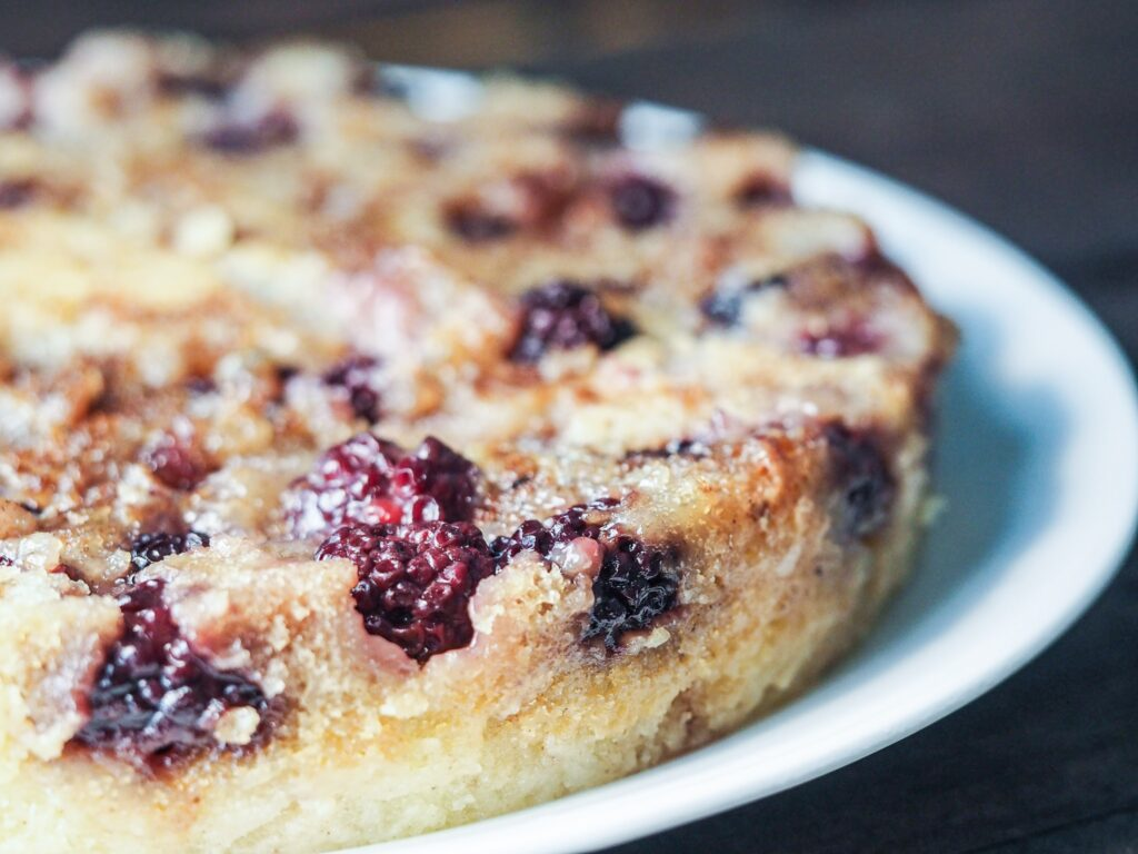close view of blackberry cobbler on white plate