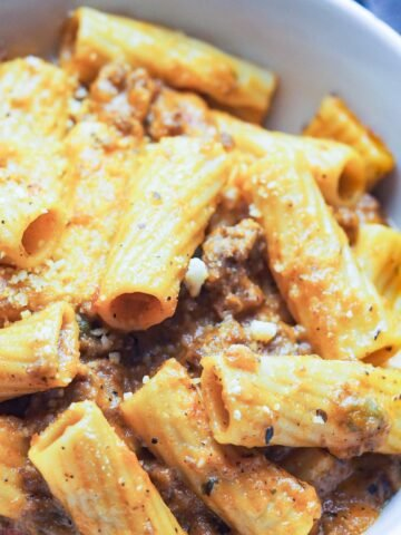 overhead shot of ziti with pramesan cheese sprinkled on top in a bowl