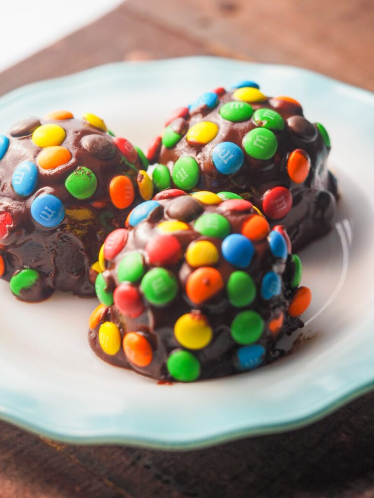 three cosmic brownie bites on white ribbon plate with blue edge