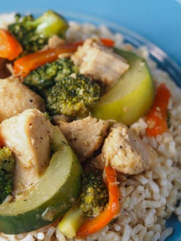 chicken stir fry on bed of rice on blue plate