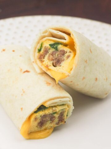 close view of breakfast burrito cut in half stacked on each other on white plate