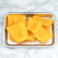 cut and cooked spaghetti squash on small metal tray on marble counter