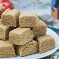 cut peanut butter fudge on white place on top of quilted christmas ornaments in front of christmas cards