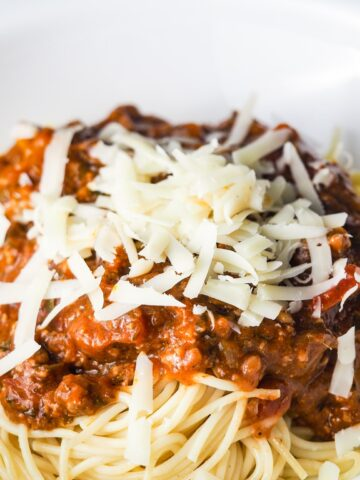 close view of spaghetti topped with red meat sauce and fresh grated parmesan cheese