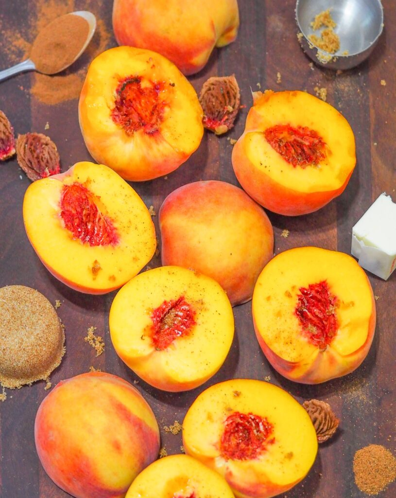 overhead shot of halved and pitted peaches on dark brown cutting board surrounded by pits, spices, butter, and brown sugar