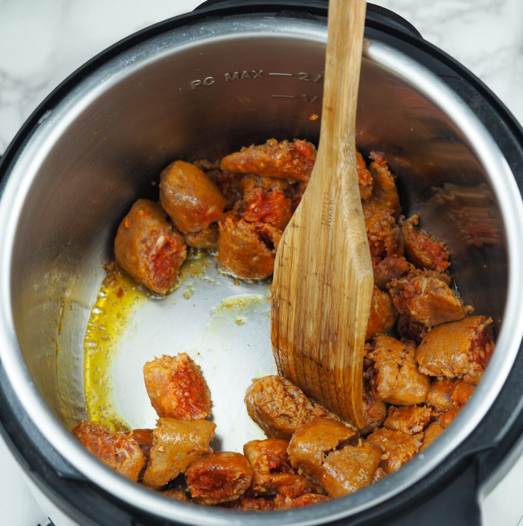 overhead view of cooking chunked Italian sausage in the Instant Pot on saute with wooden spatula