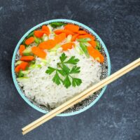 bowl of coconut rice on black textured background in bowl with blue edge garnished with sliced carrots and green onions with parsley, chop sticks resting on bottom right of bowl