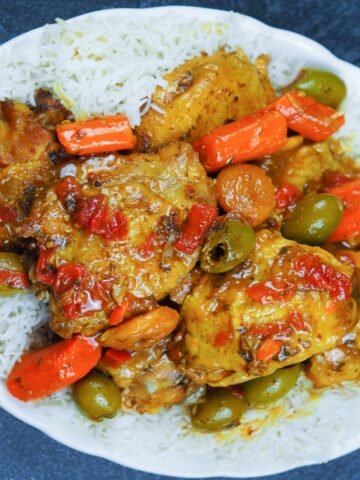 chicken tagine on a bed of rice on white oval platter with scalloped edges on black textured tabletop