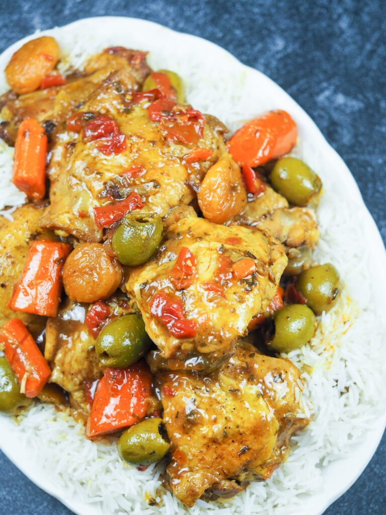 Chicken Tagine on a bed of coconut rice on white oval platter