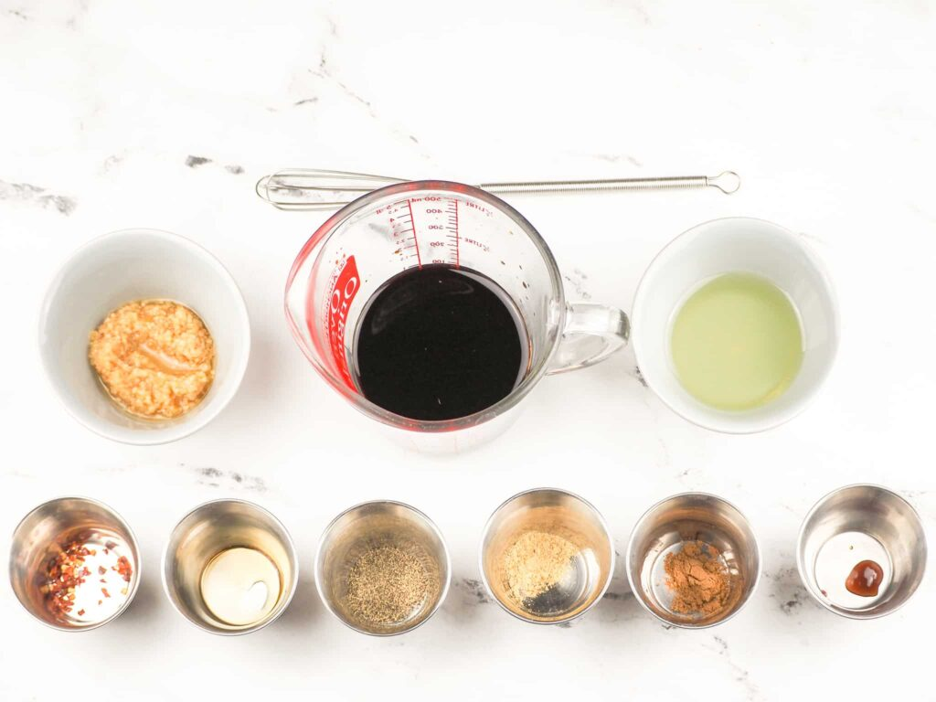 marinade ingredients set out on marble countertop with small whisk