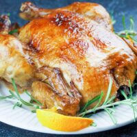 roasted whole chicken on white platter surround by orange quarters and fresh rosemary on black background