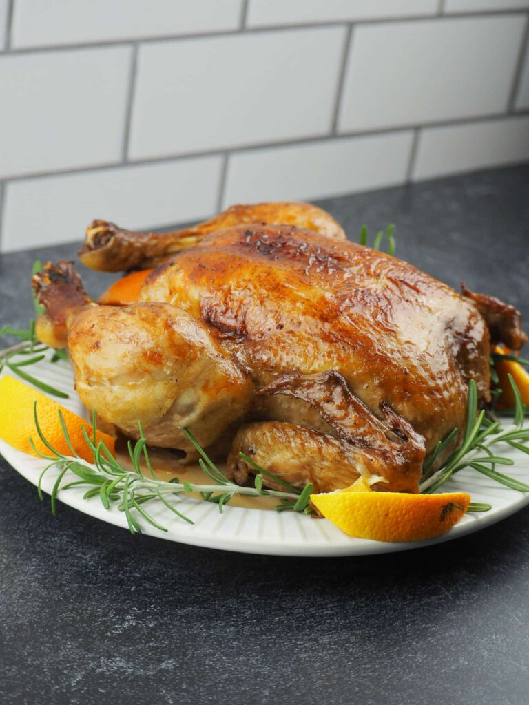 side view of roasted chicken on white plate with quartered oranges and fresh rosemary