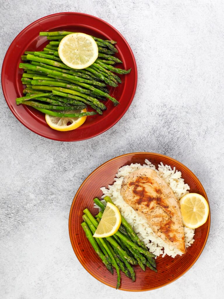 overhead view of two plates one in bottom right of chicken on bed of rice with asparagus and top left corn red plate with asparagus