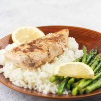 lemon chicken on jasmine rice with asparagus with lemon slices on red dinner plate