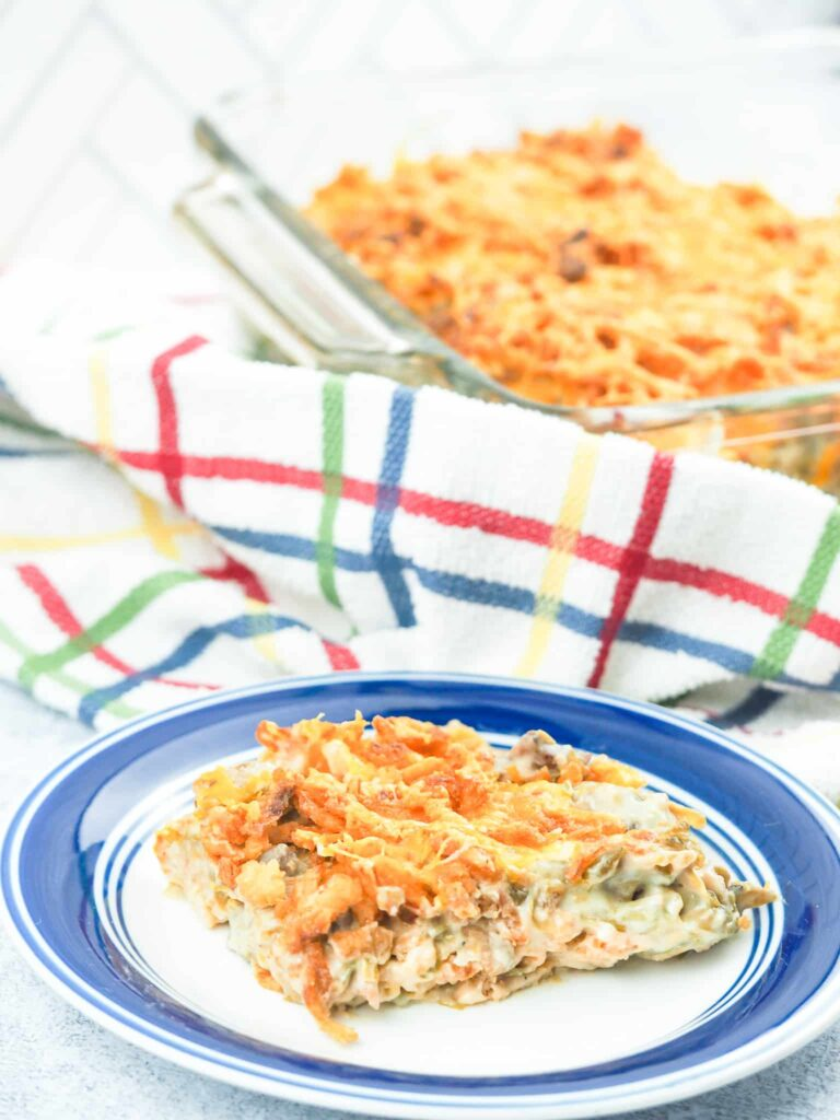green bean casserole on blue rimmed plate in foreground with casserole pan in upper right and multi colored dish towel between on counter