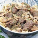 close view of beef tips with mushroom gravy served over egg noodles in blue bowl with white interior