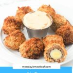 air fryer scotch eggs on white plate with dipping sauce in metal cup with one egg cut in half facing the camera