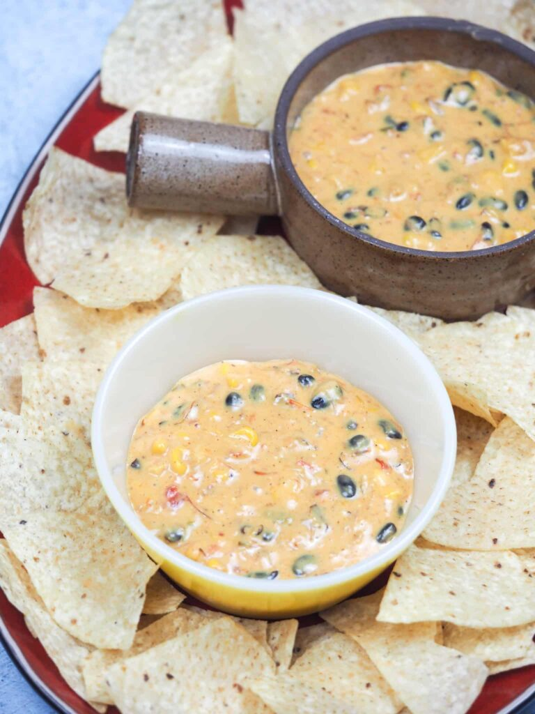 two serving bowls of queso dip on red platter with chips