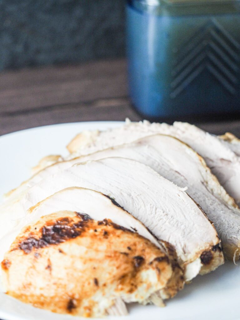 Sliced turkey on white plate with cobalt blue gravy boat in top right background