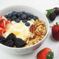 yogurt in white bowl on granite counter top next to berries topped with honey, granola, and berries