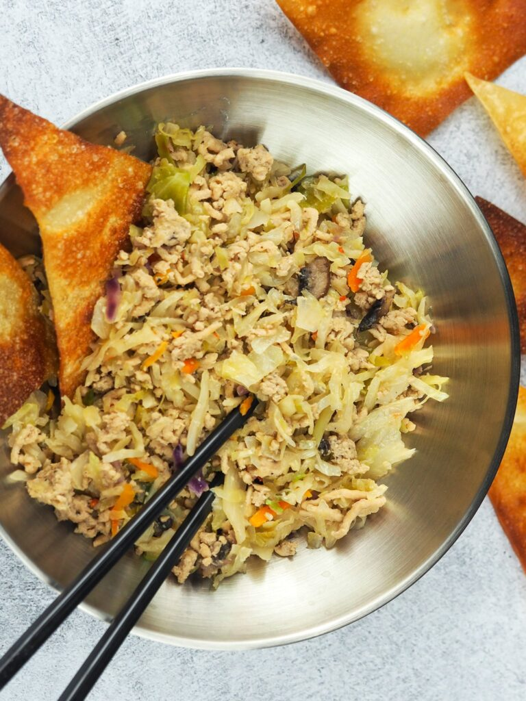 overhead close view of egg roll in a bowl in stainless steel ramen bowl with black chopsticks and egg roll chips