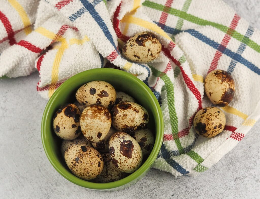 quail eggs in green cup on grey counter with multi colored towel