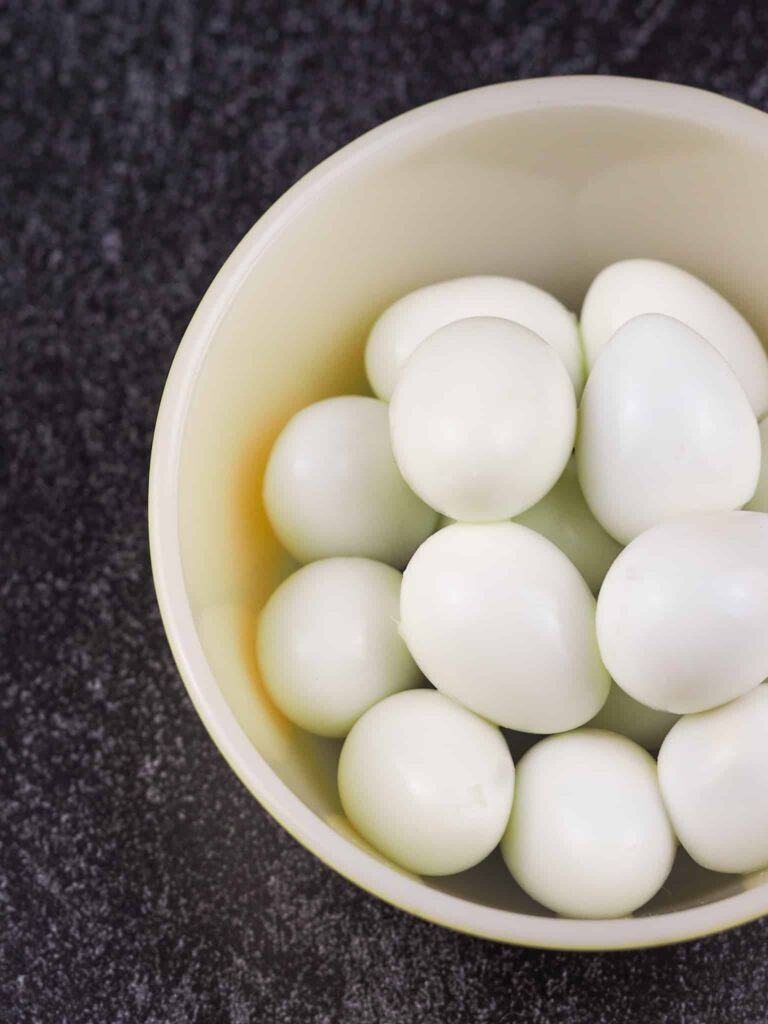 hard boiled quail eggs in white pyrex bowl on black counter