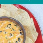 queso dip in serving bowl on red platter surrounded by tortilla chips
