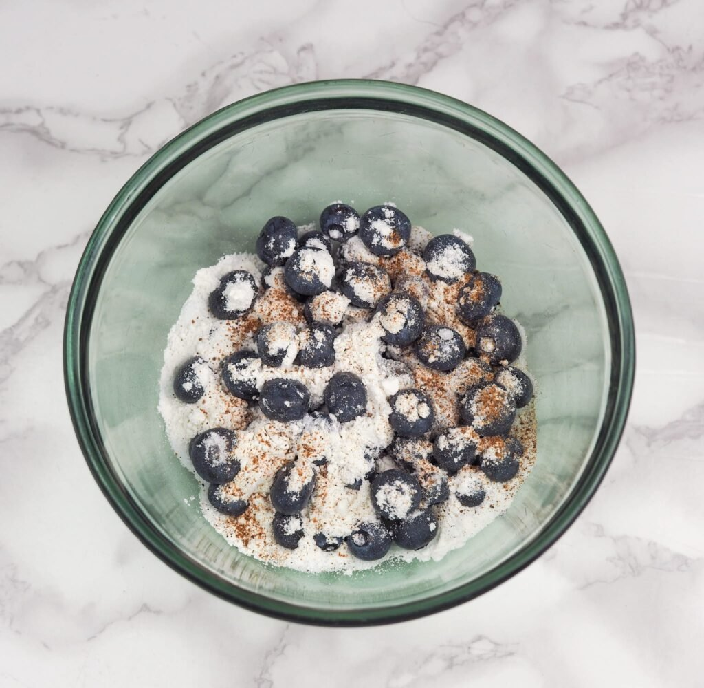 blueberry topping ingredients in clear green glass bowl on marble counter top