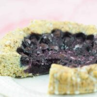 lemon blueberry poppy seed cake on white plate side view with cut out piece